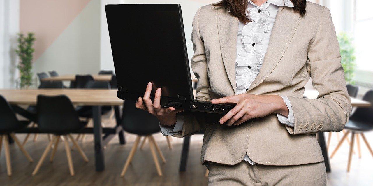 Une femme debout avec un ordinateur dans les mains