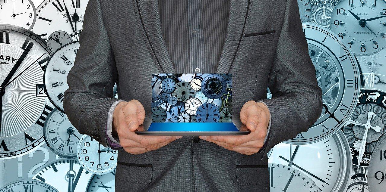Un homme qui tient une tablette avec plein d'horloges derrière