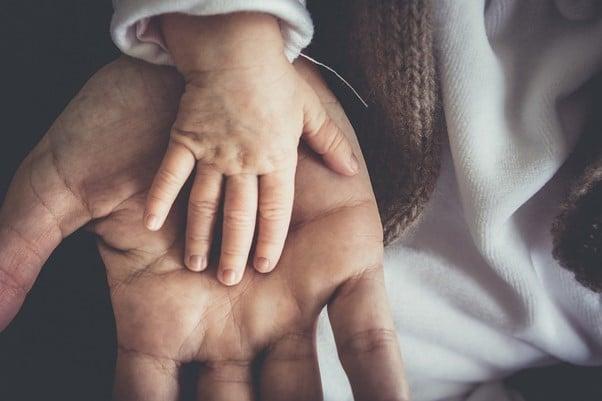 la main d'un bébé dans celle d'une maman