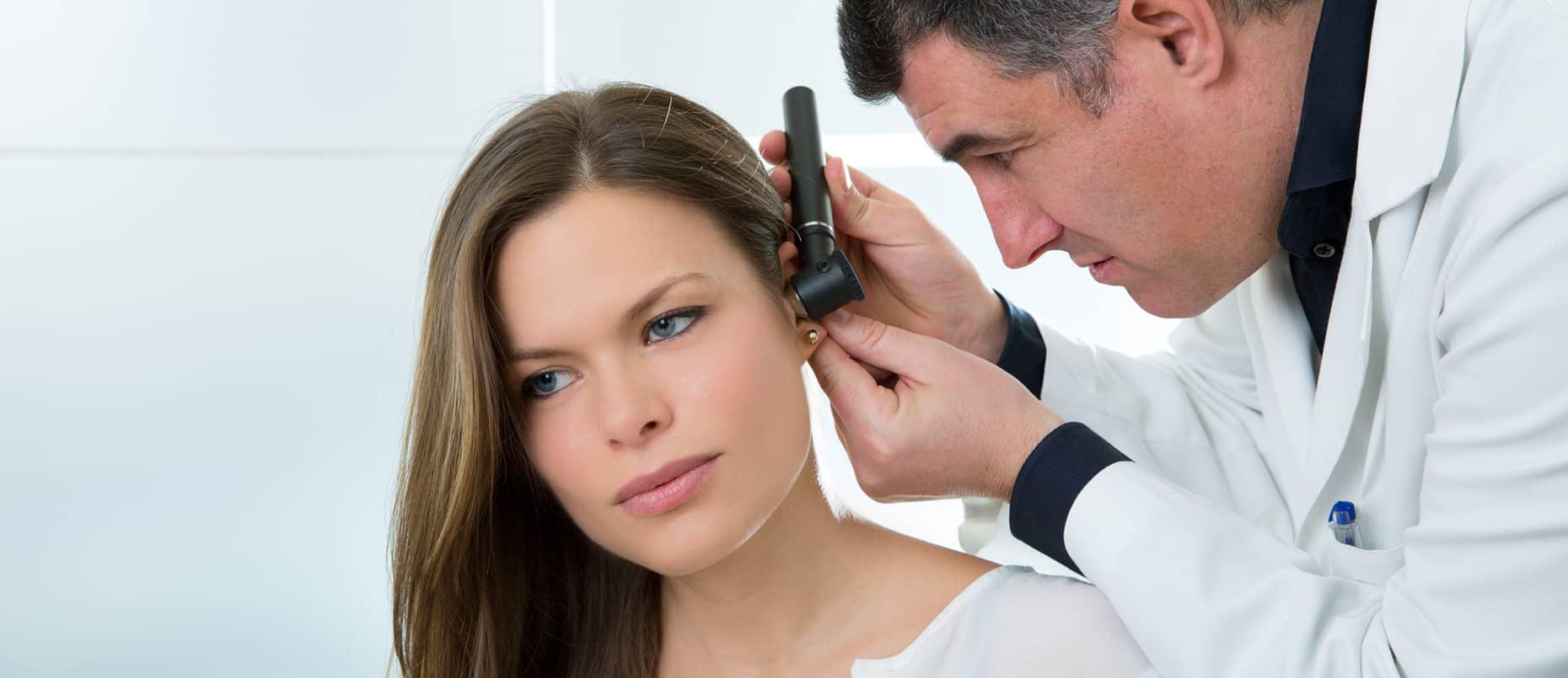 Un médecin soignant sa patiente dont l'oreille est bouchée
