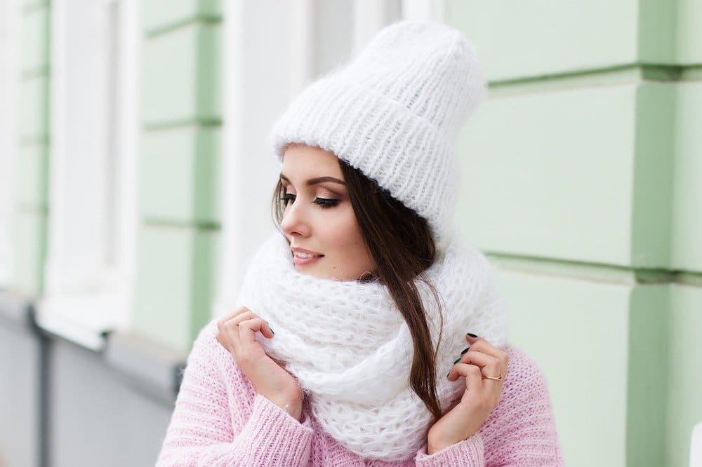 Jolie femme avec une écharpe tube blanche en laine à grosses mailles