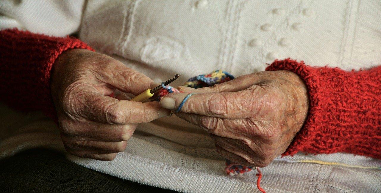 Les mains d'une personne âgée qui tricote